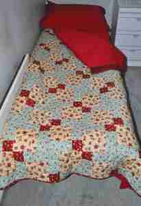 Teal and red disappearing nine patch quilt on a camp bed
