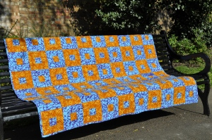 Blue, orange and yellow batik quilt with boxed squares design