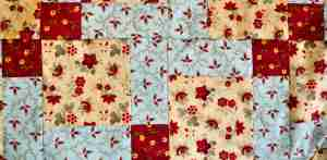 Quilt to be used as a picnic blanket sewn in disappearing nine patch design