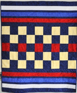 Original design of crib quilt in white, red, yellow and various blue colours