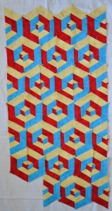 Red, yellow and blue 3D looking small quilt.
