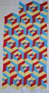 Small quilt layout of 3D affect cubes in red, yellow and blue fabric.